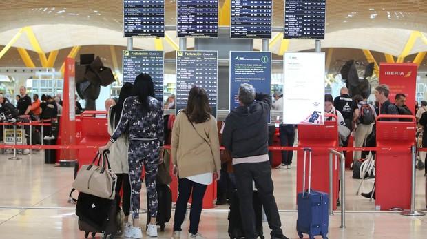 Cuatro turistas observan las pantallas de información del aeropuerto