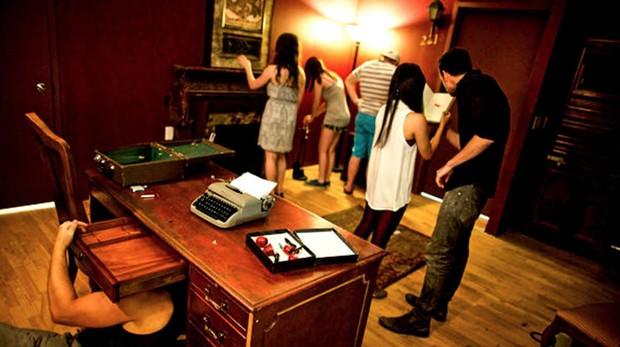 Un grupo de amigos busca pistas para resolver un enigma en una sale de «escape room»