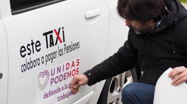 El diputado Rafa Mayoral coloca una pegatina en un taxi
