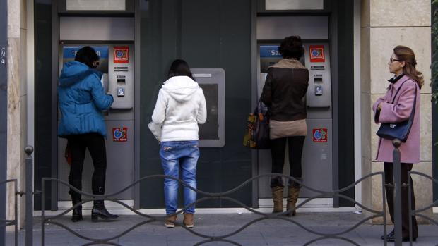 Varios usuarios utilizando cajeros automáticos de una oficina bancaria