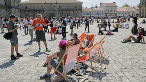 Peregrnos en la plaza del Obradoiro disfrutando de la jornada soleada de este domingo
