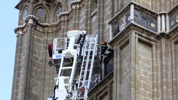 Bomberos, con una autoescala, revisan las cornisas de la torre de la catedral de Toledo