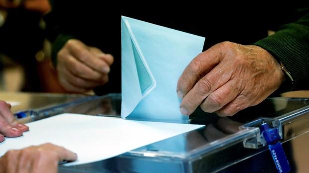 Un ciudadano deposita su voto en un centro electoral en el centro de Madrid