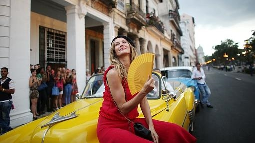 La modelo Gisele Bündchen posa sobre un almendrón cubano