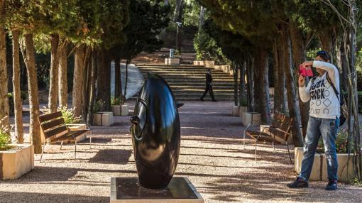 Una turista fotografía una de las esculturas expuestas en los jardines