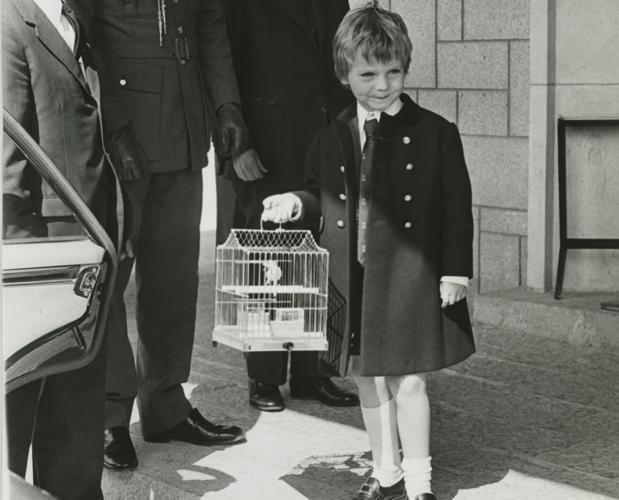 El Príncipe de Asturias, con cinco años, en el aeropuerto de Barajas, tras regresar de una visita oficial a Canarias con un canario en la jaula