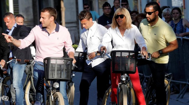 Emmanuel y Brigitte Macron posan para los medios mientras dan un paseo junto a Benalla (amarillo)