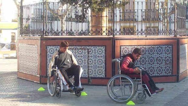 Niños jugando en su silla de ruedas.