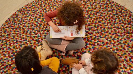 Olivia leyendole el cuento a Marta y a María, su hermana pequeña