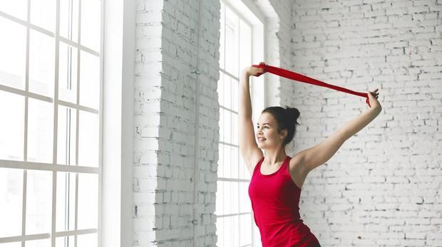 Una mujer practicando ejercicios con gomas elásticas.
