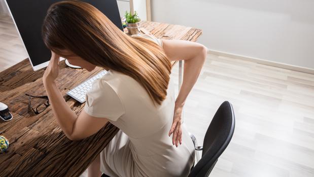 Una mujer, frente al ordenador, con dolor de espalda.