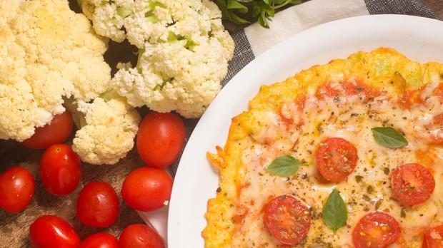 Pizza con base de coliflor y con tomates cherry.