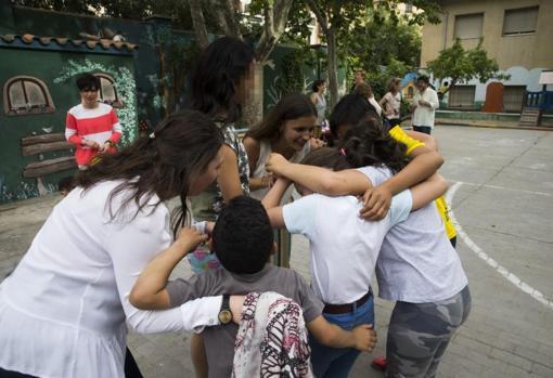 Varias voluntarias juegan con los niños tutelados en el patio de la residencia Vallehermoso