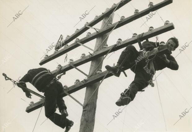 Obreros de teléfonos reparando las comunicaciones destrozadas por los facciosos...