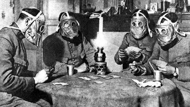 En previsión de un ataque «químico», estos soldados juegan a las cartas cubiertos con unas rudimentarias máscaras antigás