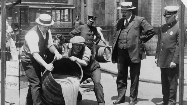Un grupo de agentes vacía un tonel con alcohol durante el periodo en el que estuvo vigente la Ley Seca