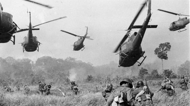 Helicópteros del ejército de EE. UU. Lanzan fuego de ametralladora contra una línea de árboles para cubrir el avance de las tropas terrestres del sur de Vietnam en un ataque contra un campamento del Vietcong