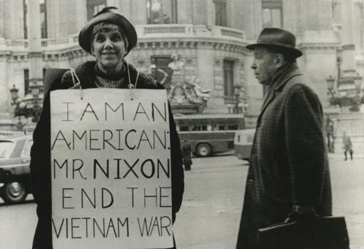La madre del jugador de ajedrez Bobby Fischer, en frente de la opera de París, con un cartel pidiendo a Richard Nixon el fin de la Guerra de Vietnam (1973)