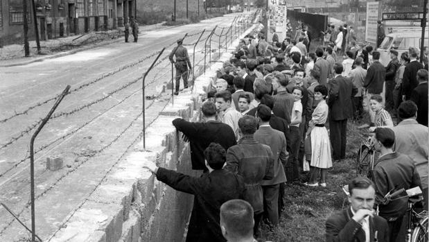 A la derecha Muro de Berlín, un grupo muy numeroso de berlineses occidentales contemplan con curiosidad el aspecto desolado de una de las calles de Berlín Oriental, en 1961
