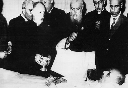 El cardenal Eugene TIsserant imparte su bendición al Papa Pío XII en la cámara mortuoria