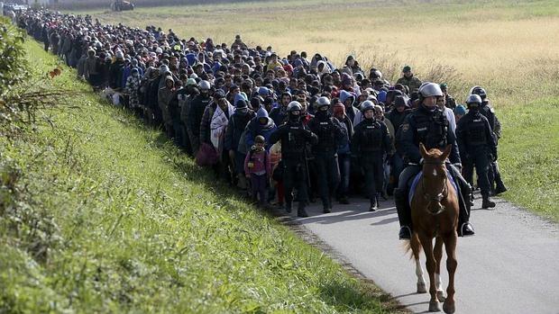 Un policía dirige a un grupo de refugiados cerca de Dobova, en Eslovenia