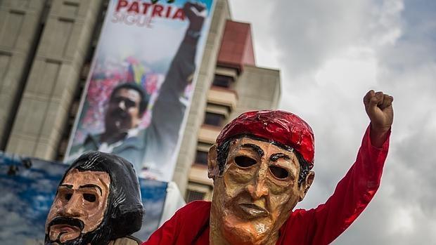 Seguidores de los candidatos del Partido Socialista Unido de Venezuela (Psuv) acuden a un acto de cierre de campaña de las municipales de diciembre de 2013 con máscaras de Ernesto Che Guevara (i) y Hugo Chávez