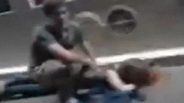Un joven socorre a una mujer herida en el exterior de la sala Bataclan