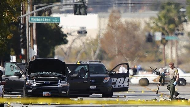 Un policía sostiene una de las armas encontradas en el lugar del tiroteo