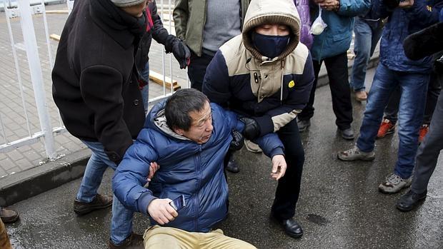 Uno de los manifestantes, en el suelo, mientras le intentan obligar a levantarse