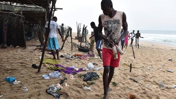 Un hombre limpia la playa de Grand Bassam tras el tiroreo ayer en un resort en el que fueron asesinadas por Al Qaida 16 personas
