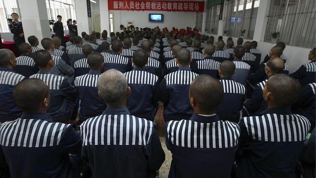 Un grupo de presos chinos ve la televisión
