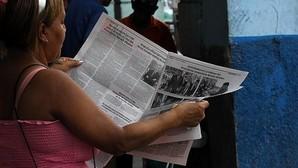 Una mujer lee el diario oficial Granma donde se aprecia la noticia de la visita del presidente de los Estados Unidos