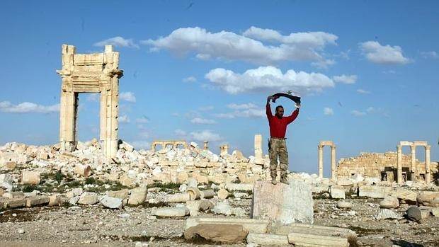 Un soldado sirio junto a los daños causados por Daesh en la histórica ciudad de Palmira (Siria)