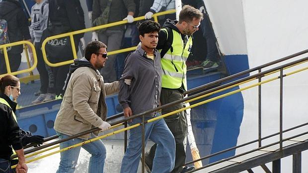 Personal de Frontex acompaña ayer a un refugiado en un ferry turco que sale de la isla griega de Lesbos