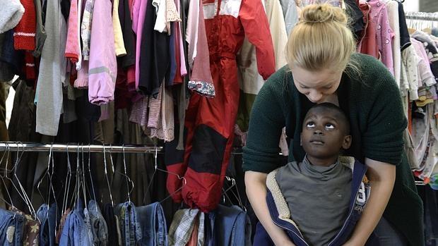 Una trabajadora social viste a un niño refugiado en un centro de recogida de ropa de Munich