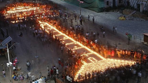Vigilia celebrada ayer en Katmandú, recordando un año después del terremoto la Torre Dharhara y el templo Kasthamand, dibujados con velas, destruidos por el seísmo que causó la muerte de 9.000 personas