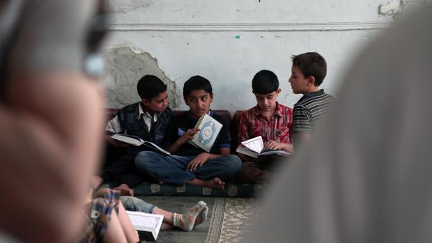 Niños musulmanes leen el Corán, su libro sagrado