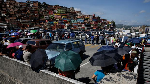 Varios venezolanos hacen cola para entrar en un supermercado de Caracas