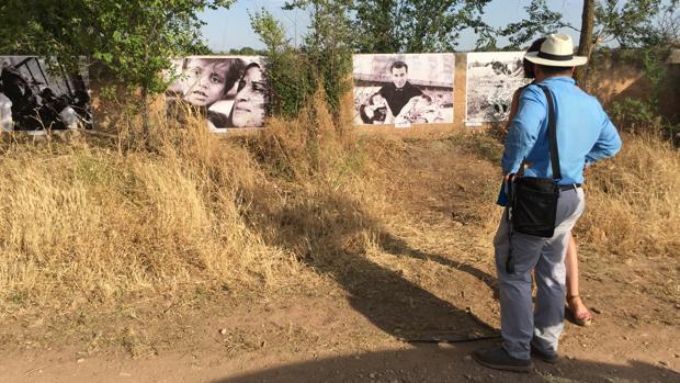 Un hombre contempla una de las fotografías expuestas en «Fotos en el camino: refugiados»