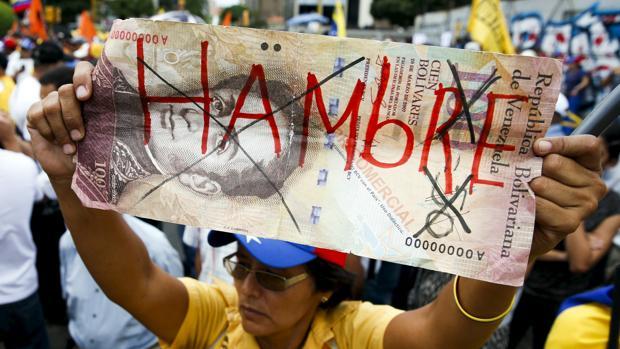 Una mujer sostiene un billete gigante de 100 bolívares en el que pone «Hambre»