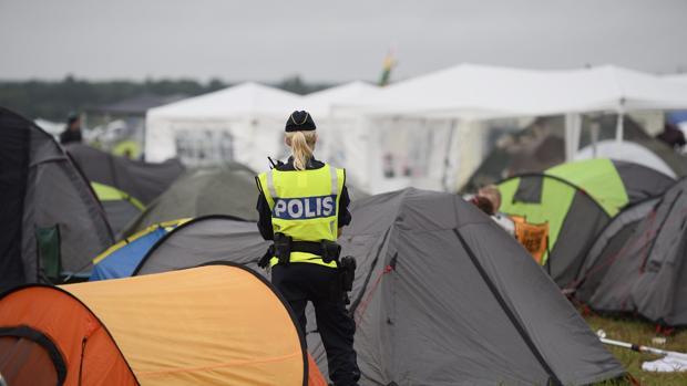 Una agente de policía permanece en guardia en la zona de acampada del festival de Bravalla en Suecia