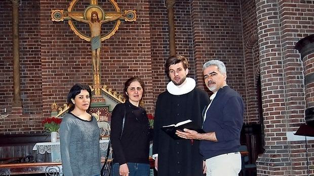 Tres conversos iraníes con un pastor luterano en la iglesia Apostelkirken de Copenhague - Journal de Genève