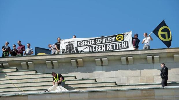 Miembros de un grupo de extrema derecha se manifiesta en la Puerta de Brandemburgo de Berlín
