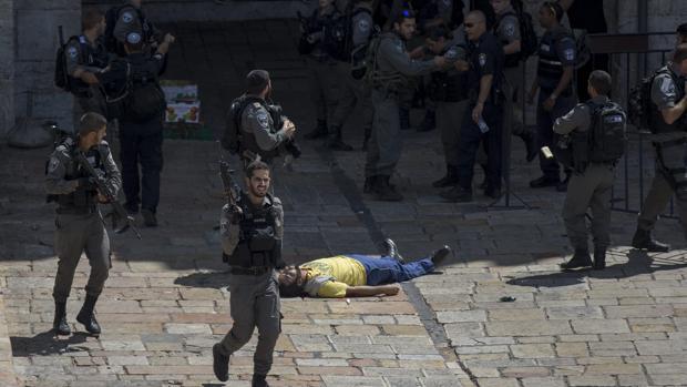 Policías rodean el cuerpo sin vida de un joven abatido a tiros tras presuntamente atacar con un cuchillo a agentes junto a la muralla de la ciudad vieja en Jerusalén (Israel)
