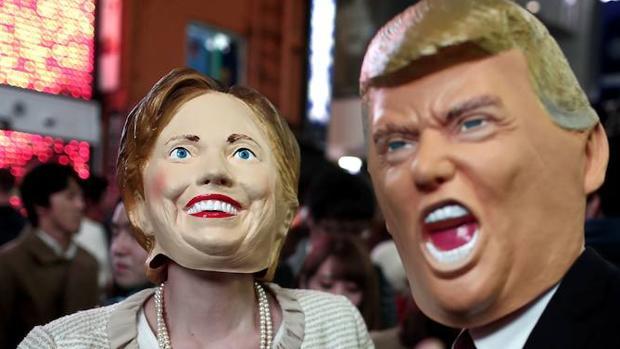Dos personas posan disfrazadas de la candidata demócrata y del candidato republicano