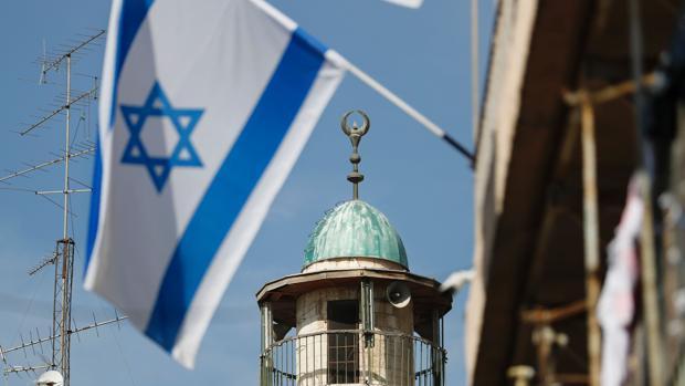 La bandera de Israel ondea junto al minarete de una mezquita en el barrio árabe de la ciudad vieja de Jerusalén