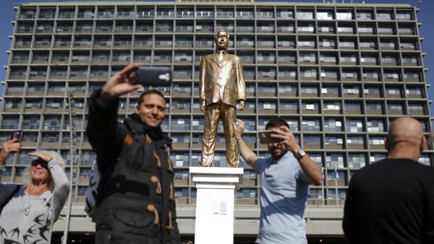 Un grupo de personas se acerca para ver una estatua dorada que representa al primer ministro israelí, Benjamín Netanyahu,