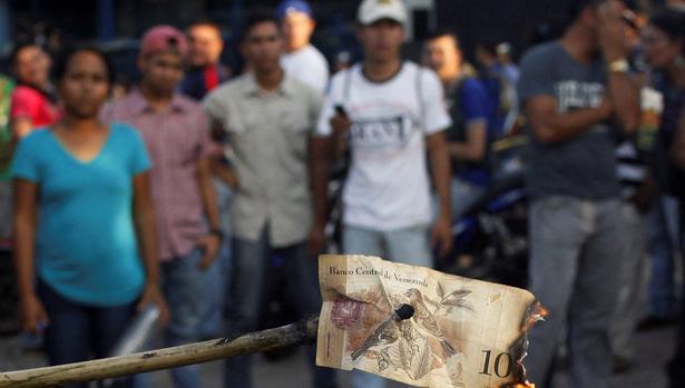 Unos venezolanos queman un billete de cien bolívares, durante una protesta en El Pinal