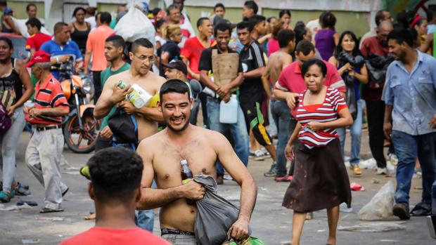 Un grupo de saqueadores con víveres robados de un supermercado de Ciudad Bolívar este sábado
