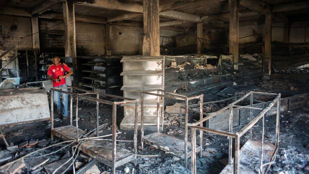 Un hombre inspecciona un almacén quemado por los saqueadores en Ciudad Bolívar, en estado Bolívar